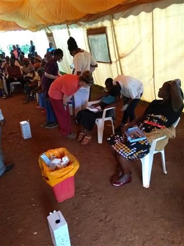 Pacjenci w mobilnej klinice w Marani, leczeni na ogrodowych krzesłach.